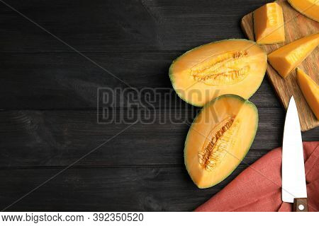 Tasty Fresh Cut Melon On Black Wooden Table, Flat Lay. Space For Text
