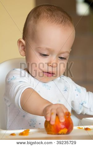Curious Baby Boy Examines A Peach
