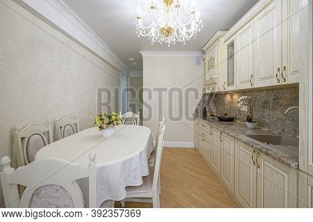 Luxury modern neoclassic beige kitchen interior with locker and dining table