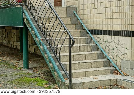 Black Iron Handrails With A Forged Pattern On The Stairs With Gray Concrete Steps Against A Brown Wa