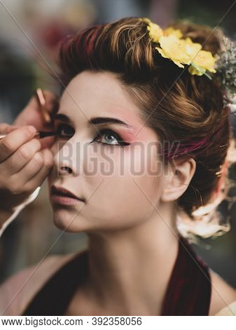 Portrait of a beautiful woman in beauty salon. Makeup artist applies eyeliner on a face