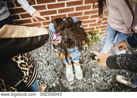 Sad Intimidation Moment. Girl Sit On The Ground Bullying In Schoolyard