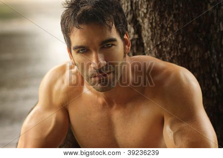 Sexy masculine man shirtless outdoors against tree