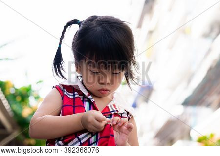 Girl Is Practicing Buttoning Up Her Clothes By Herself. Child Is Wearing A Red Dress. Kid Is Deliber