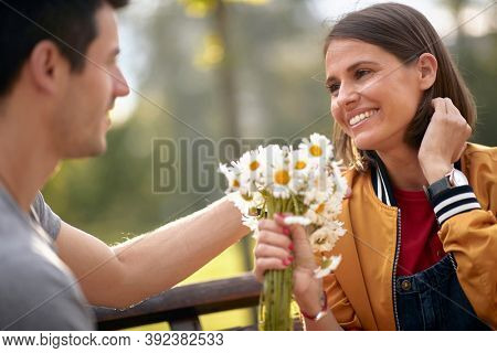 Man giving bouquet of flowers to a woman in a park; Happy couple concept