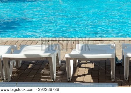 White Sun Loungers By The Pool With Blue Bright Water, Copy Space.