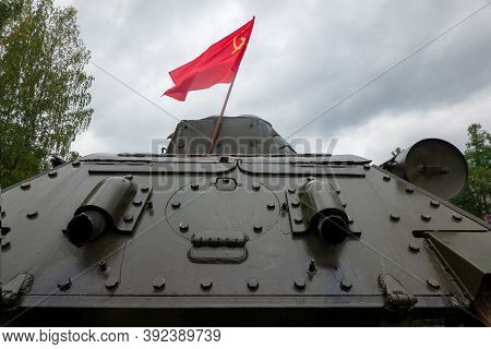 The Red Soviet Flag Is Installed Behind The Turret Of The T-34 Tank. Back View. There Are Trim Eleme