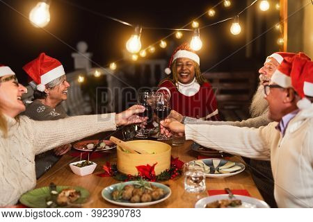 Happy Multiracial Senior Friends Toasting With Red Wine Glasses During Christmas Holidays Dinner Cel