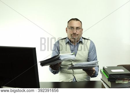 The Male Office Worker Makes A Helpless Gesture. A Lot Of Office Clerk Work