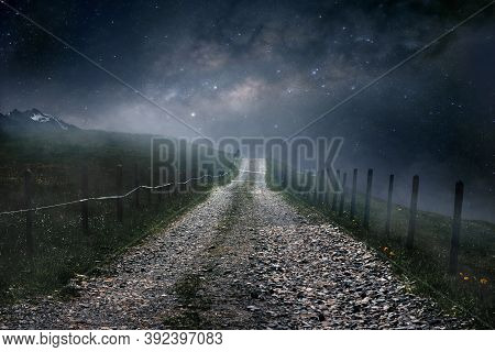 Milky Way Galaxy Above Night Landscape. Lonely Gravel Path Leading Towards Milky Way In The Distance