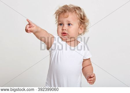 Caucasian Baby Pointing With Index Finger Away, Sees Something Interesting, Wearing T Shirt, Standin