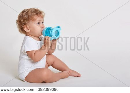 Portrait Of Cute Toddler Drinking Water From Bottle While Sitting Against White Wall, Wearing Body S