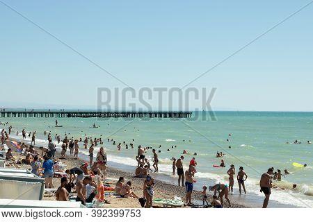 Crimea, Yalta - 1 September 2020: People On Sandy Beach Of Sea With Blue Bright Water, Illustrative