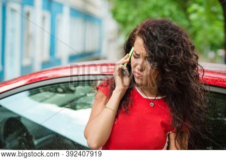Portrait Of An Angry Woman Calling Insurance On Phone After Car Breakdown Wearing Red Shirt Outdoors