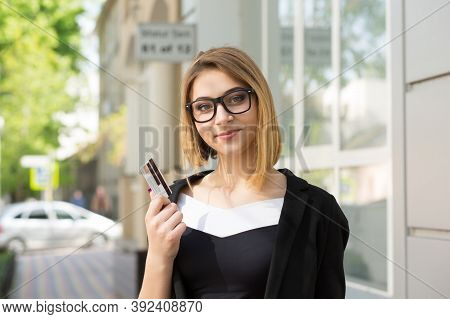 Cheerful Woman With Slight Smile On Face Holding Showing Credit Loyalty Card Near Store Shopping Mal