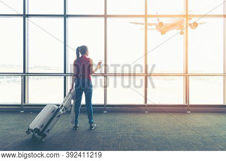 Traveler Woman Plan And Backpack See Airplane Flight At The Airport Glass Window, Girl Tourist Happy