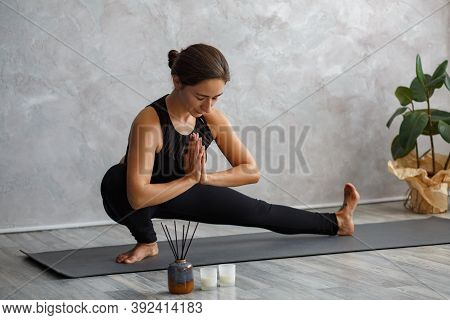 Portrait Of Sporty Young Woman Doing Exercises On Yoga Lesson At Home.beautiful Girl Practicing Side