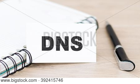 Dns, Domain Name System, Text On White Card Next To Notepad And Pen On Table