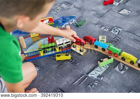 Child Play With Wooden Train, Build Toy Railroad At Home Or Kindergarten. Toddler Kid Play With Wood