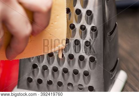 Woman Is Rubbing Cheese On Grater. Cooking, Food And Home Concept - Close Up Of Female Hands Grating