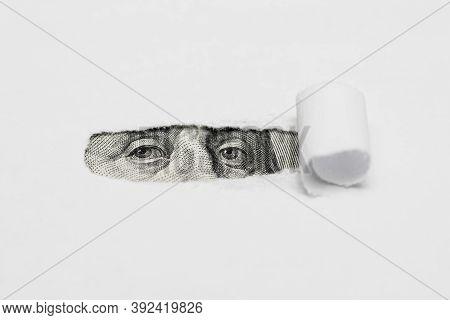 Benjamin Franklin Macro Peeking Through Torn White Paper. Portrait Of Benjamin Franklin, Is Depicted