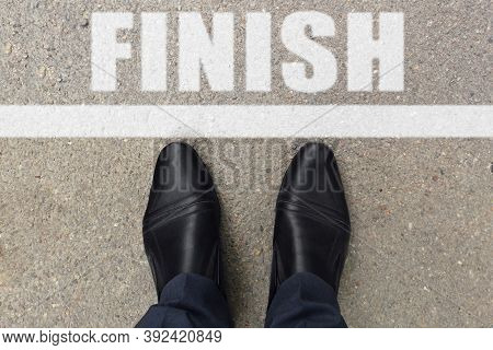 Business Concept. Top View Of Shoes Standing On Asphalt Road With Line And Word Finish. Black Shoes