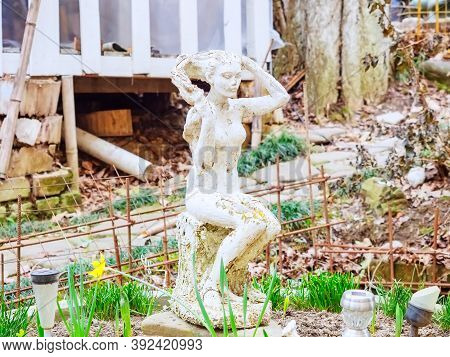 Russia, Sochi 18.02.2020. Peeling Statue Of A Seated Girl In An Unkempt Abandoned Courtyard
