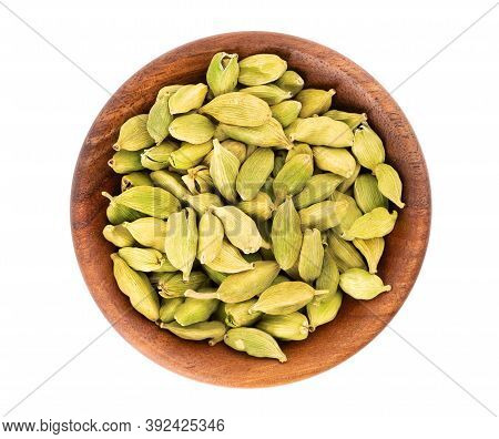 Cardamom Seeds In Wooden Bowl, Isolated On White Background. Pile Of Green Cardamom. Top View.