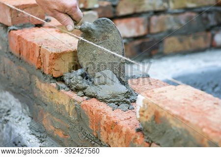 Bricklayer Using Trowel To Tap A Brick Level. Hand White-wash Cement Built Wall Brick New House, Bri