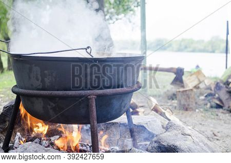 Large Metal Cauldron Over A Fire. A Tourist Fire On Which Water Is Boiled For Food. Camp Pot, Boilin