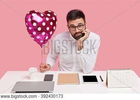 Lonely Unshaven Male Holds Chin, Has Discontent Expression, Holds Valentine, Wears White Shirt, Has