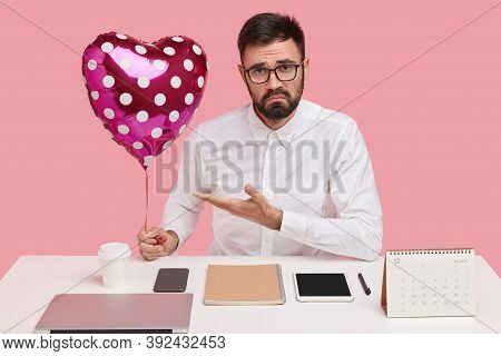 Discontent Unshaven Man Demonstrates Valentine Or Balloon, Has Unhappy Expression, Wears Spectacles
