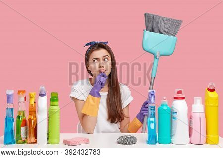 Pretty Housemaid Has Intention, Looks Thoughtfully Aside, Dressed In Caual Clothes, Holds Broom, Doe