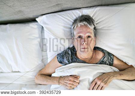 Senior Aged Woman On Bed At Home Feeling Sad