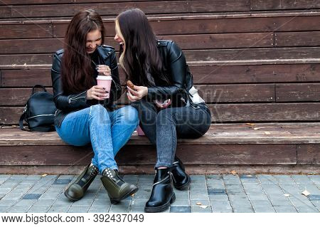 Two Female Student Friends On The Wooden Steps Near The University On The Street In Jeans And Leathe