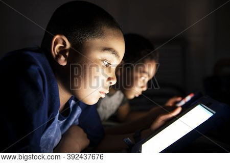 Two Little Boy, Lay In A Dark, Playing With Tablet On The Bed