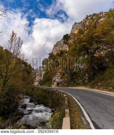 Fall Color Forest And Rocky Cliffs With A Winding Mountain Road Next To A Small River