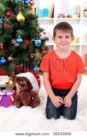 Little boy sits near Christmas tree