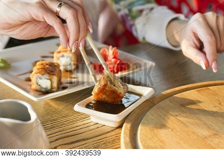 Young Woman Eating Sushi Roll In A Restaurant