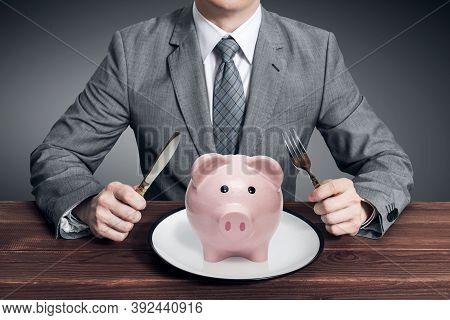 Businessman Eating Piggy Bank. Business Concept. Businessman Going To Eat Piggy Bank