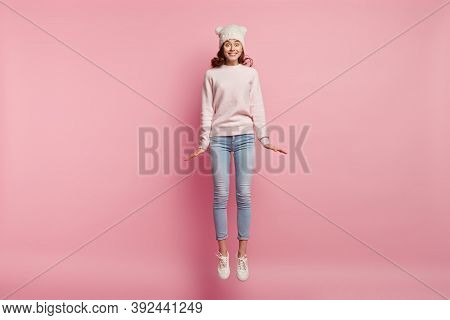 Life Is Good Concept. Pleased Energetic Satisfied Woman In Casual Clothes And Headgear, Jumps High,
