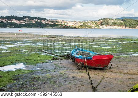 Lonely Wooden Boat Stranded During Low Tide At The Well-preserved Village Of Combarro In Ponteveda,