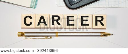 The Word Career Is Written On Wooden Cubes, On Top Of A Calculator, Bottom Of A Pen