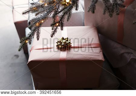Merry Christmas! Stylish Wrapped Christmas Gift Box Under Christmas Tree With Lights In Room