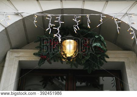 Stylish Christmas Branches With Red Berries And Lantern, Modern Ornaments On Store Front Or Building