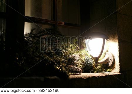Stylish Decorated Windows With Christmas Branches, Lantern Light And Pine Cones In Evening. Christma