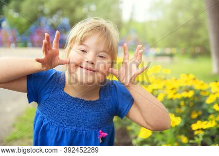 A Portrait Of Trisomie 21 Child Girl Outside Having Fun On A Park Giving Some Grim