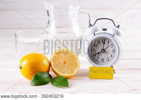 Intermittent Fasting. Fasting Time, Alarm Clock And Lemon Water On White Table, Diet Food Concept.
