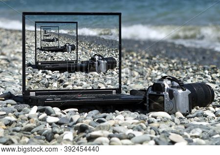 The Droste Effect Concept: Laptop And Camera On The Beach With Picture Recursively Appearing Within