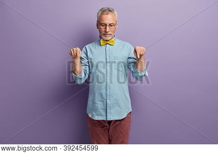 Serious Bearded Elderly Man Points Down With Both Index Fingers, Shows Product, Promots Copy Space D